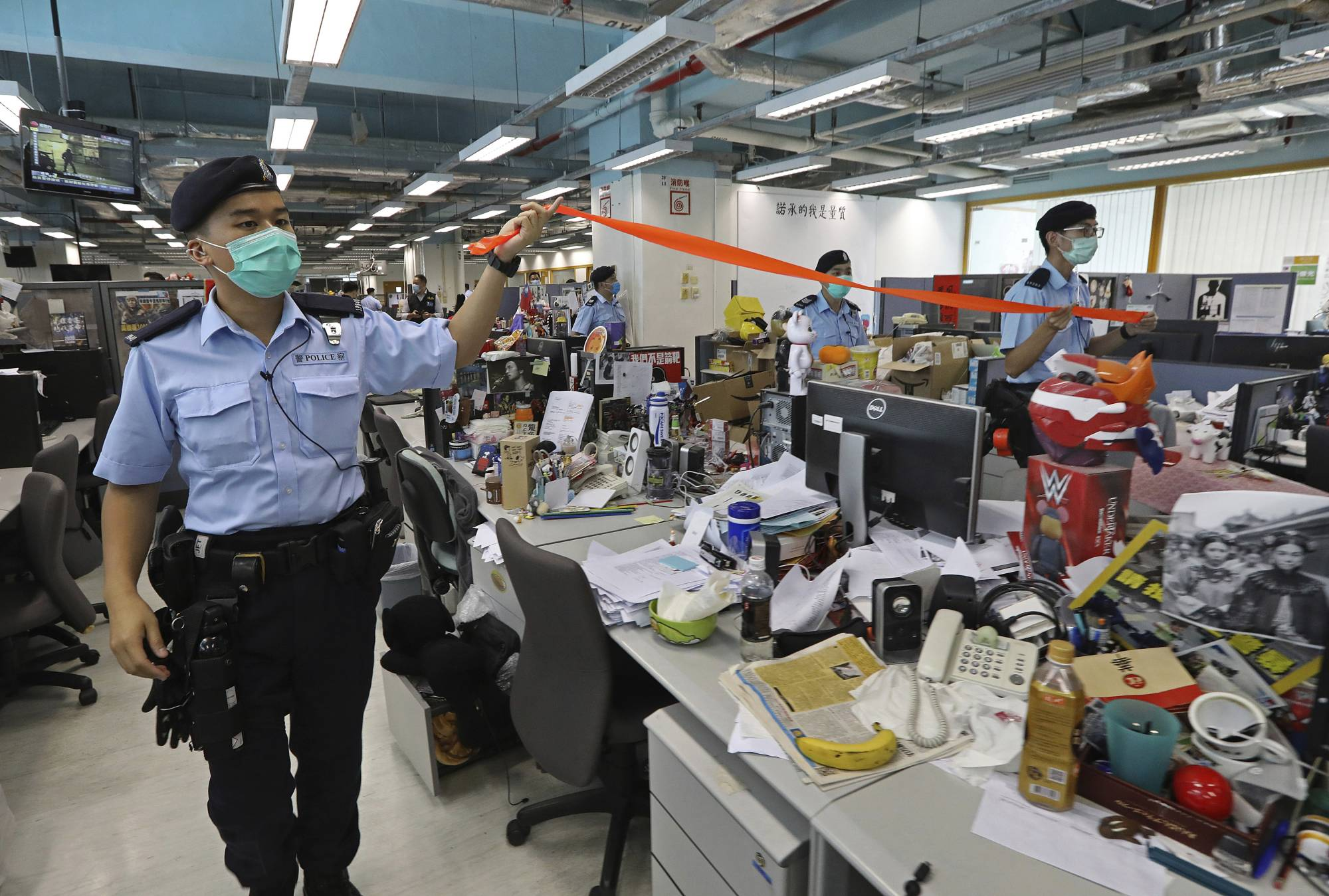 Hong Kong police officers enter the Apple Daily headquarters on the day the newspaper's founder, Jimmy Lai, was arrested. | Apple Daily / via AP